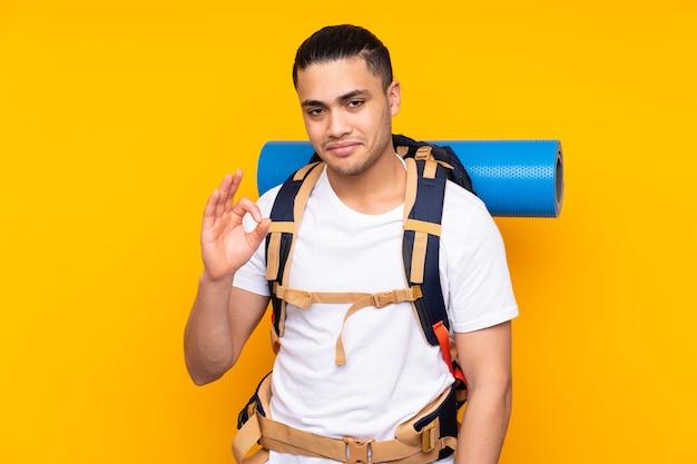 Jeune homme asiatique alpiniste avec un gros sac à dos isolé sur fond jaune montrant un signe ok avec les doigts