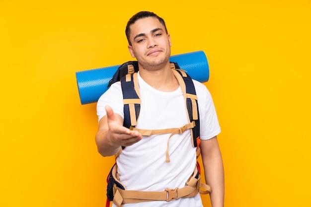 Jeune homme asiatique alpiniste avec un gros sac à dos isolé sur fond jaune poignée de main après une bonne affaire
