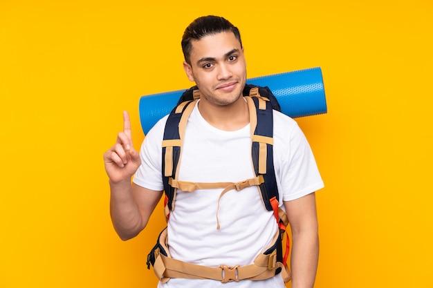 Jeune homme asiatique alpiniste avec un gros sac à dos isolé sur fond jaune pointant avec l'index une excellente idée