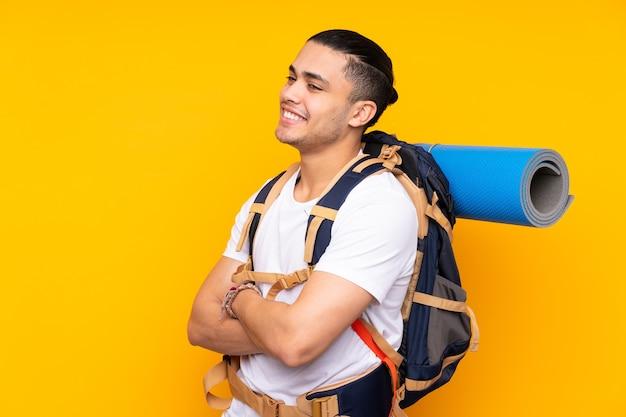 Jeune homme asiatique alpiniste avec un gros sac à dos isolé sur fond jaune à la recherche sur le côté