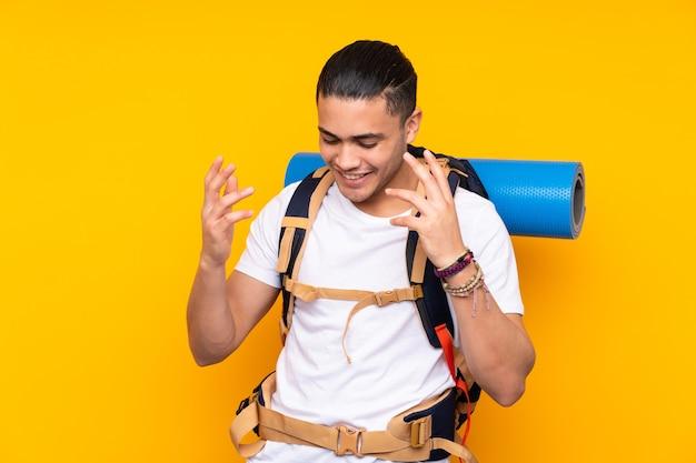 Jeune homme asiatique alpiniste avec un gros sac à dos isolé sur fond jaune en riant