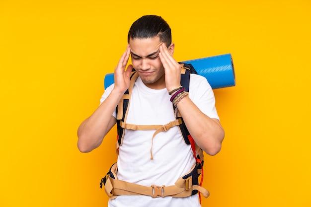 Jeune homme asiatique alpiniste avec un gros sac à dos isolé sur un mur jaune malheureux et frustré par quelque chose. expression faciale négative