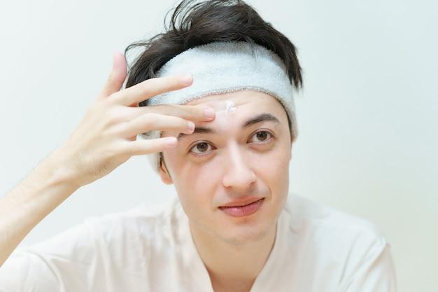 Jeune homme asiatique appliquant la crème à son visage