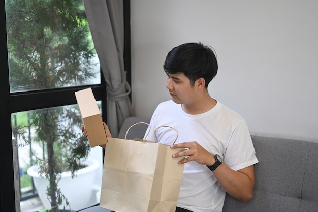 Jeune homme asiatique assis sur un canapé et ouvrant une boîte-cadeau.