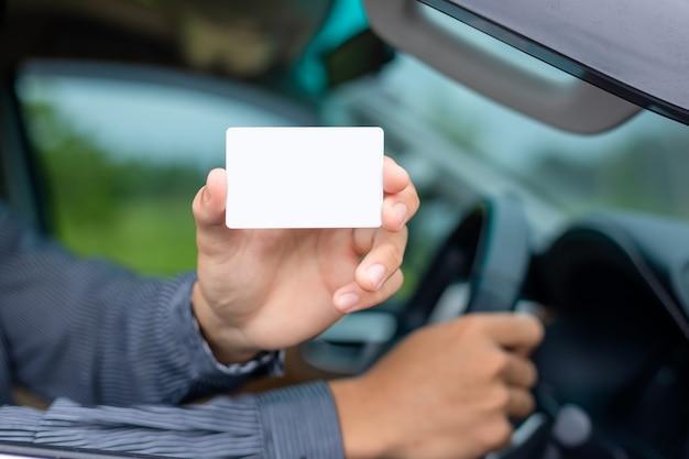 Jeune homme asiatique assis dans la voiture moderne et tenant une carte de visite vierge