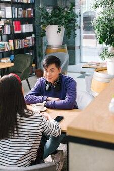 Jeune homme asiatique assis en face de la dame aux cheveux longs à la table avec une tasse de café devant lui
