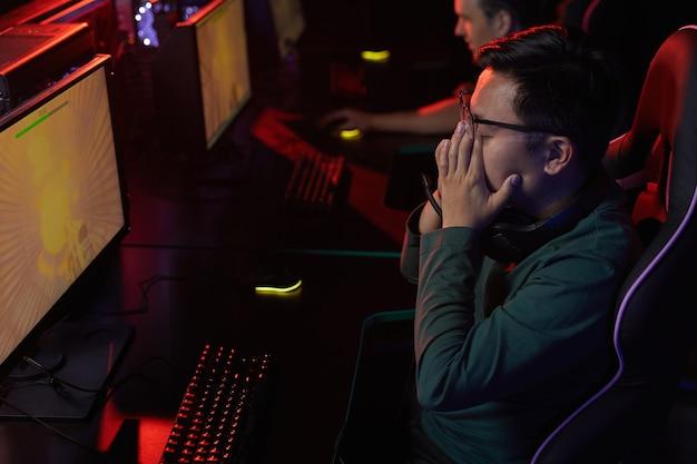 Jeune homme asiatique assis à la table devant un écran d'ordinateur, il en a assez de jouer à des jeux informatiques avec ses amis