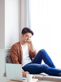 Jeune homme asiatique assis à la table devant un ordinateur portable