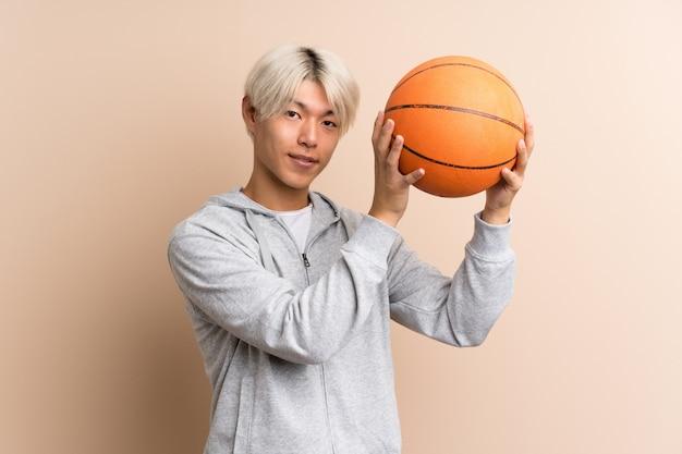Jeune homme asiatique avec une balle de basket