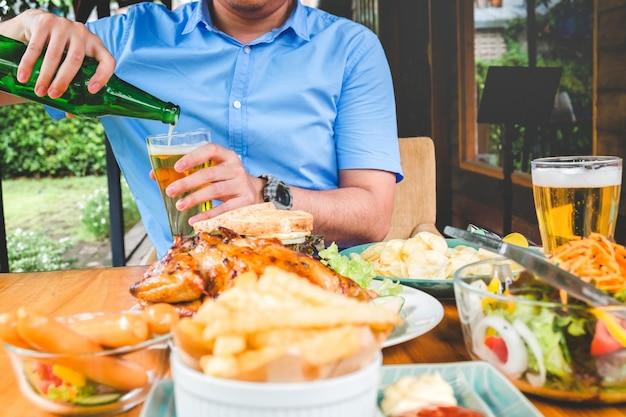Jeune homme asiatique, boire de la bière et manger des aliments heureux tout en profitant de la maison