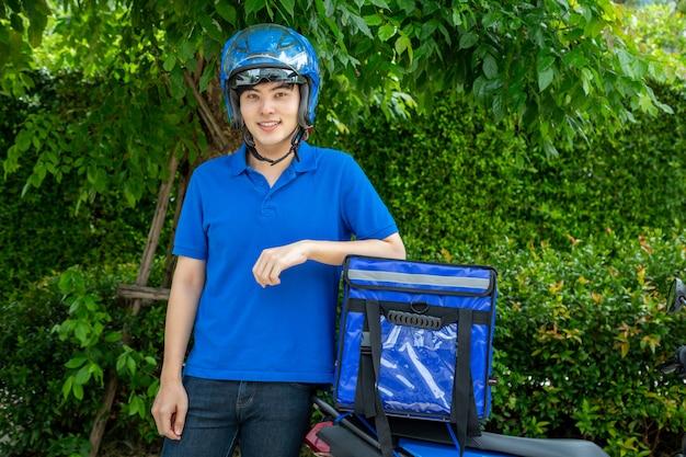 Jeune homme asiatique avec boîte de livraison, moto offrant un concept de service express alimentaire.