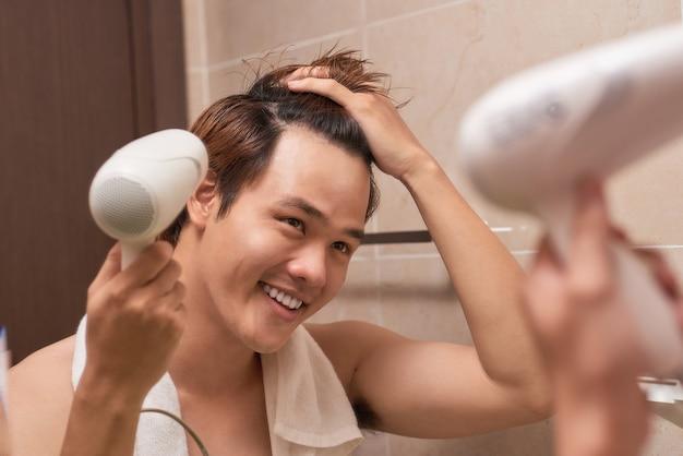 Jeune homme asiatique brushing cheveux dans la salle de bain
