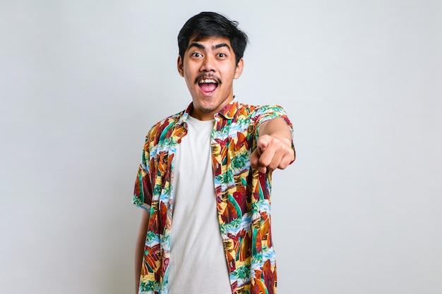 Jeune homme asiatique en chemise décontractée pointant vers l'avant, regardant la caméra, fait de votre choix un geste sur fond blanc