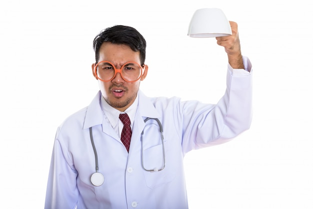 Jeune homme asiatique en colère médecin tenant une tasse de café vide