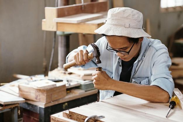 Jeune homme asiatique concentré utilisant un ciseau et un marteau lorsqu'il travaille avec une planche de bois