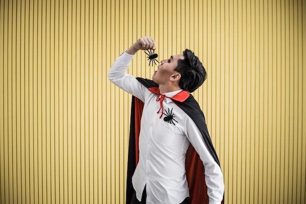 Jeune homme asiatique en costume dracula et manger une araignée noire sur fond jaune du concept d'halloween. portrait d'un homme adolescent déguisé en dracula pour célébrer le festival d'halloween.