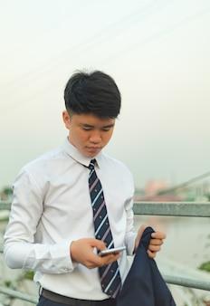Jeune homme asiatique en costume envoyant un message sur sa peau
