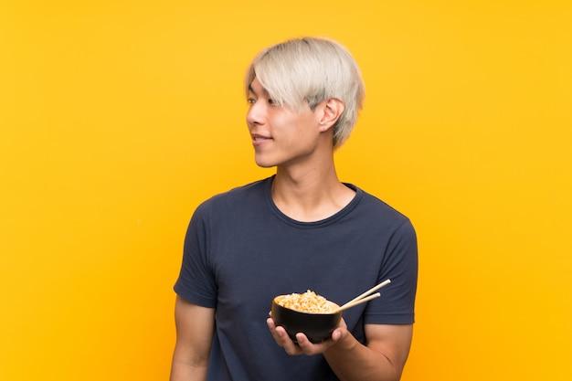 Jeune homme asiatique sur le côté isolé jaune à la recherche