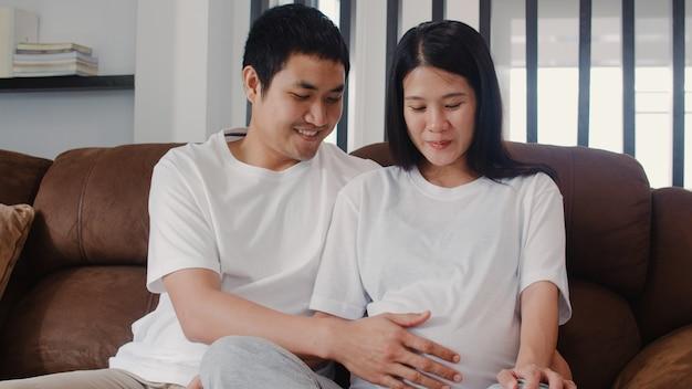 Jeune homme asiatique de couple enceinte touche le ventre de sa femme en discutant avec son enfant. maman et papa se sentent heureux, souriant, paisible, tout en prenant soin de bébé, grossesse allongée sur le canapé du salon à la maison
