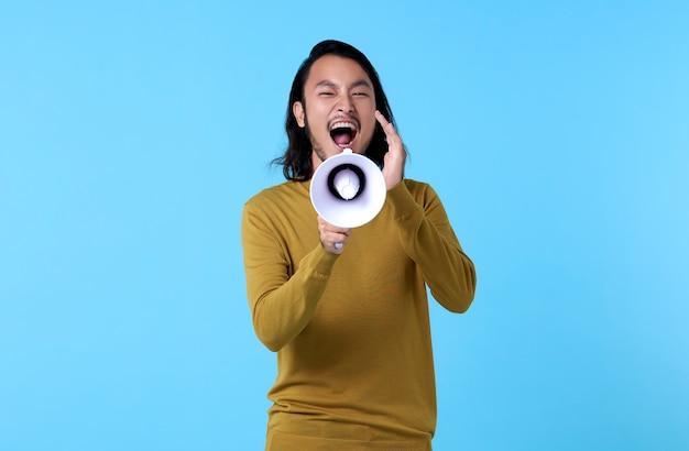 Jeune homme asiatique criant dans un mégaphone isolé sur un espace bleu.