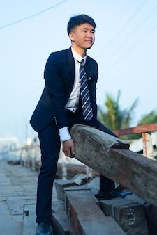 Jeune homme asiatique dans un costume formel soulevant une grosse bûche