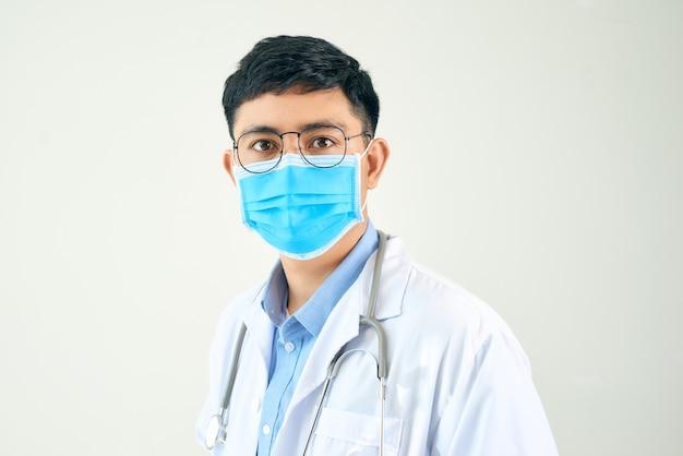 Jeune homme asiatique dans le domaine médical, portant un manteau blanc et un masque facial,