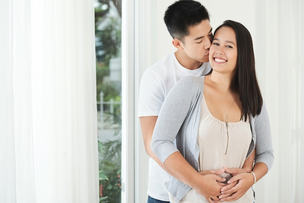 Jeune, homme asiatique, debout, derrière, petite amie, étreindre, et, embrasser, sur, joue