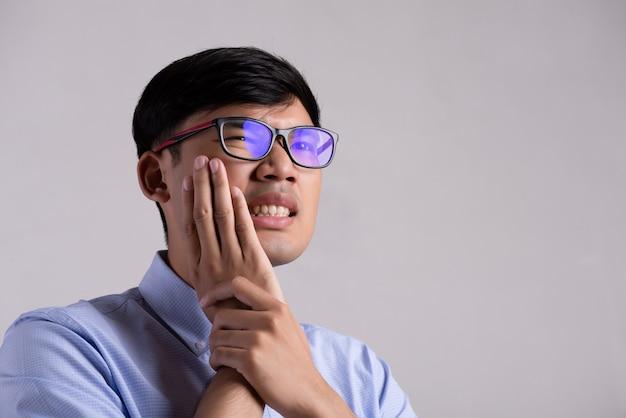 Jeune homme asiatique avec des dents sensibles ou des maux de dents. concept de soins de santé.