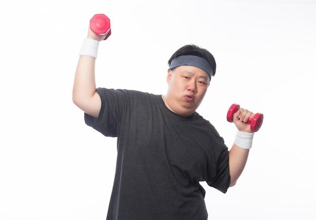 Jeune homme asiatique drôle de sport gras exercice avec haltère isolé