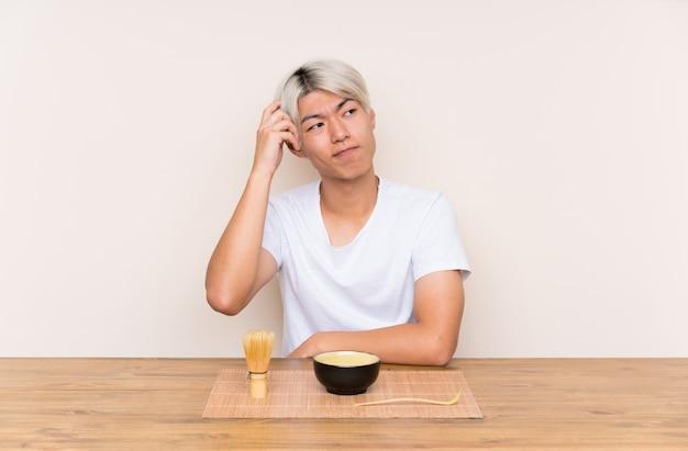 Jeune homme asiatique avec du thé matcha dans une table ayant des doutes et avec une expression du visage confuse