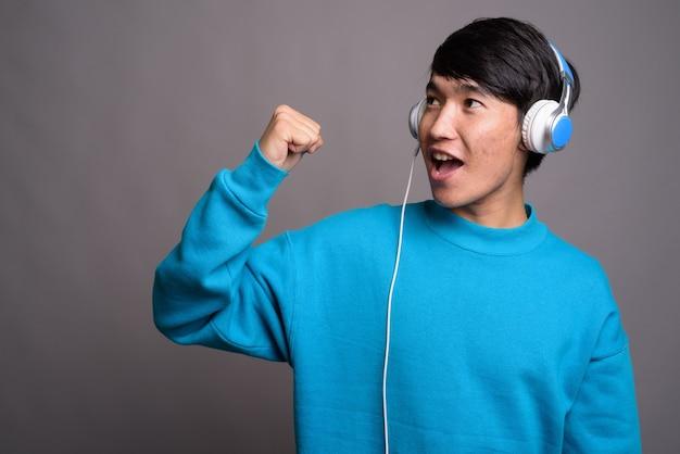Jeune homme asiatique écoutant de la musique contre un mur gris