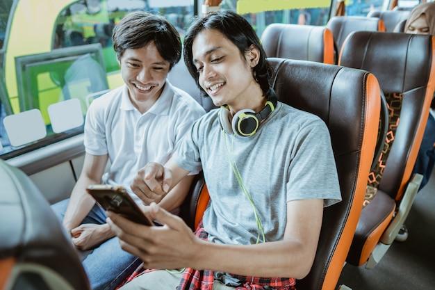 Un jeune homme asiatique avec des écouteurs et pointant du doigt tout en regardant l'écran du téléphone portable alors qu'il était assis près de la fenêtre du bus