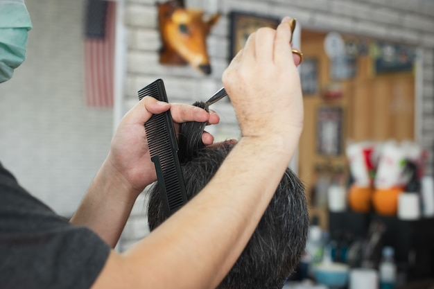 Jeune homme asiatique étant coupe de cheveux avec des ciseaux par un coiffeur professionnel en salon de coiffure. le coiffeur à l'aide d'un peigne et de ciseaux coupe les cheveux.