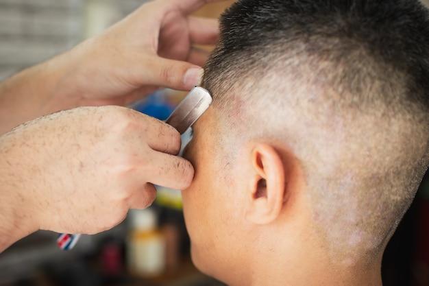 Jeune homme asiatique étant coupe de cheveux avec un rasoir par un coiffeur professionnel en salon de coiffure.