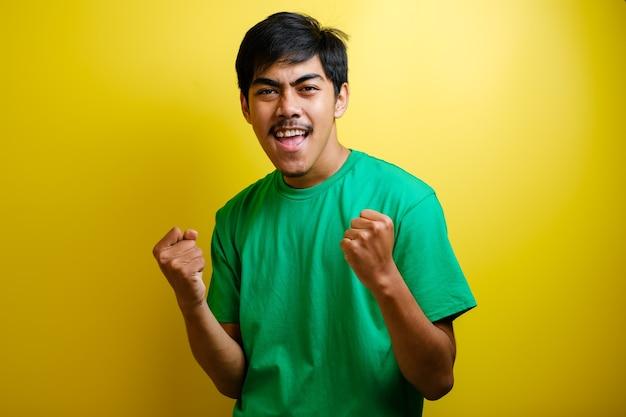 Jeune homme asiatique excité levant les poings avec un visage souriant et ravi, oui geste, célébrant le succès sur fond jaune