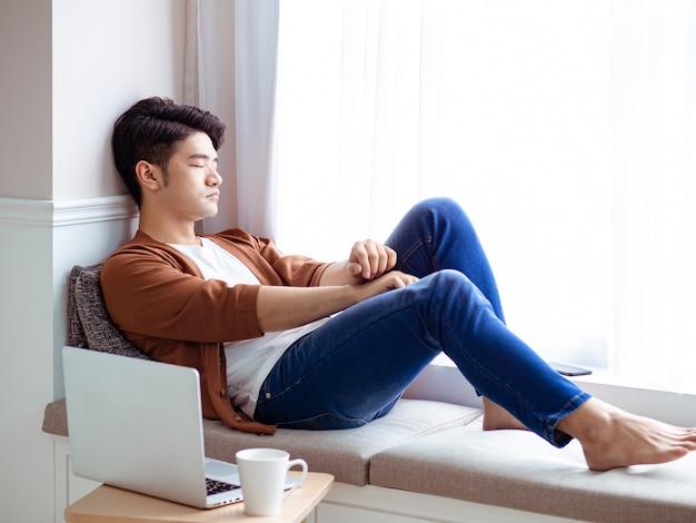 Un jeune homme asiatique fait une pause après avoir utilisé un ordinateur portable