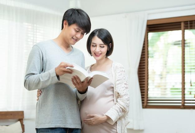 Jeune, homme asiatique, et, femme enceinte, livre lecture, dans maison