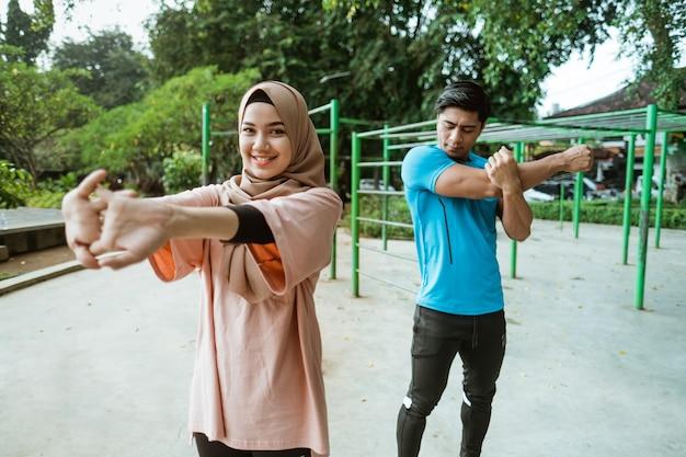 Un jeune homme asiatique et une fille dans un voile debout faisant des mouvements d'échauffement avant de faire de l'exercice dans le parc