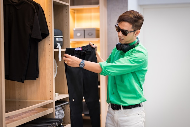 Jeune homme asiatique habillé en style décontracté et portant des lunettes et des écouteurs choisissant un pantalon