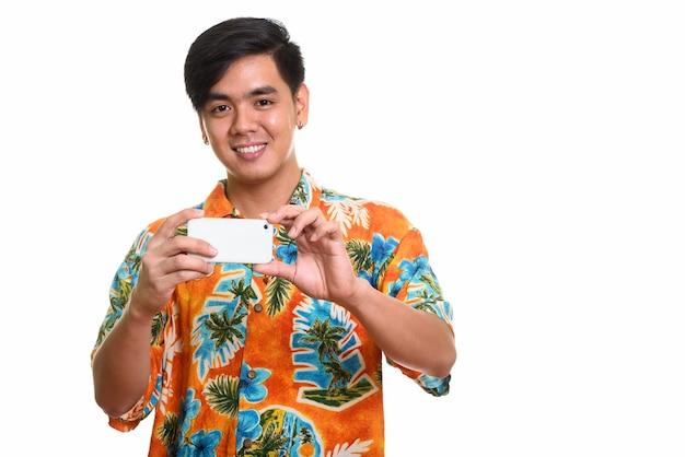 Jeune homme asiatique heureux souriant et prenant une photo avec pho mobile