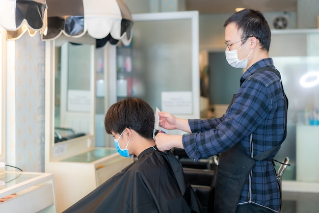 Jeune homme asiatique et homme coiffeur portant un masque médical pour se protéger pendant le roman coronavirus, covid-19 dans barbershop hair care service.