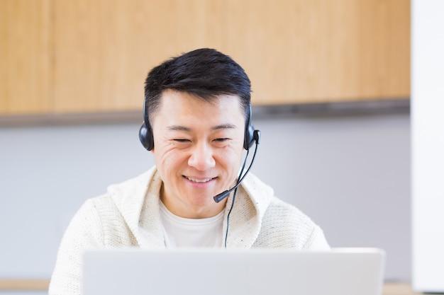 Jeune homme asiatique indépendant assis à la maison au bureau avec un casque et parlant en ligne en vidéo