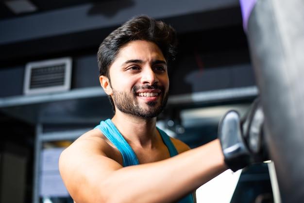 Jeune homme asiatique indien boxe dans une salle de sport avec sac de boxe avec des gants sur