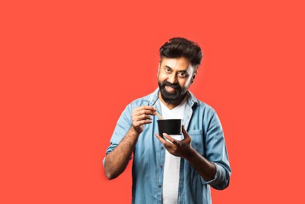Jeune homme asiatique indien mangeant des plats à emporter dans la boîte à l'aide d'une cuillère ou de baguettes, debout sur le rouge