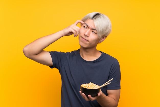 Jeune homme asiatique sur jaune isolé ayant des doutes et avec une expression du visage confuse