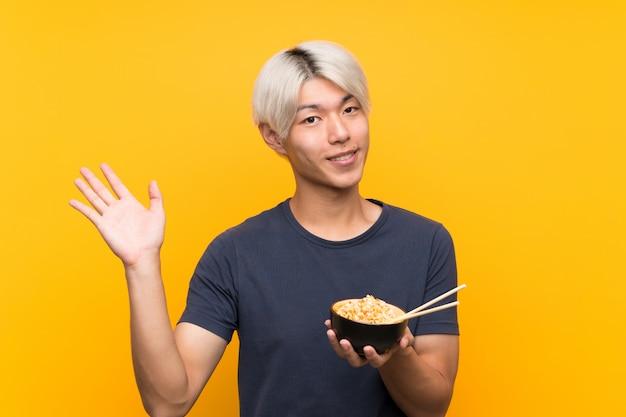 Jeune homme asiatique sur jaune isolé, saluant avec la main avec une expression heureuse