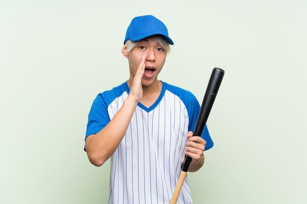 Jeune homme asiatique jouant au baseball sur vert isolé criant avec la bouche grande ouverte