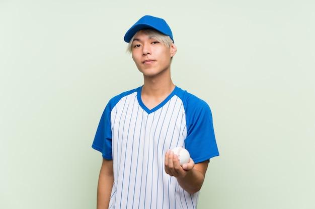 Jeune homme asiatique jouant au baseball sur vert isolé