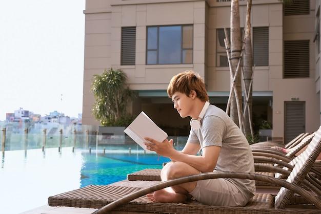 Jeune homme asiatique lisant un livre au bord de la piscine par une journée d'été ensoleillée