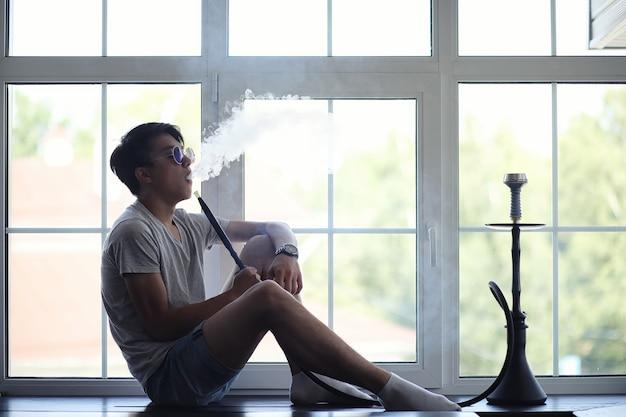 Jeune homme asiatique à lunettes de soleil fumant un narguilé à la fenêtre
